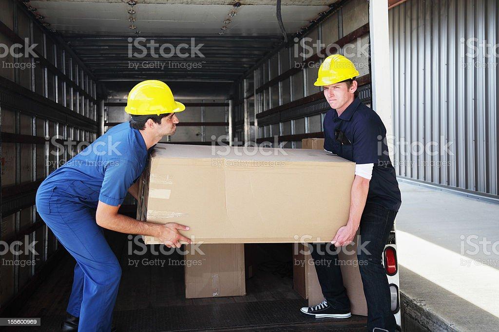 Workers Unloading Heavy Box stock photo