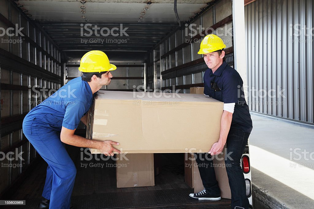 Workers Unloading Heavy Box stock photo