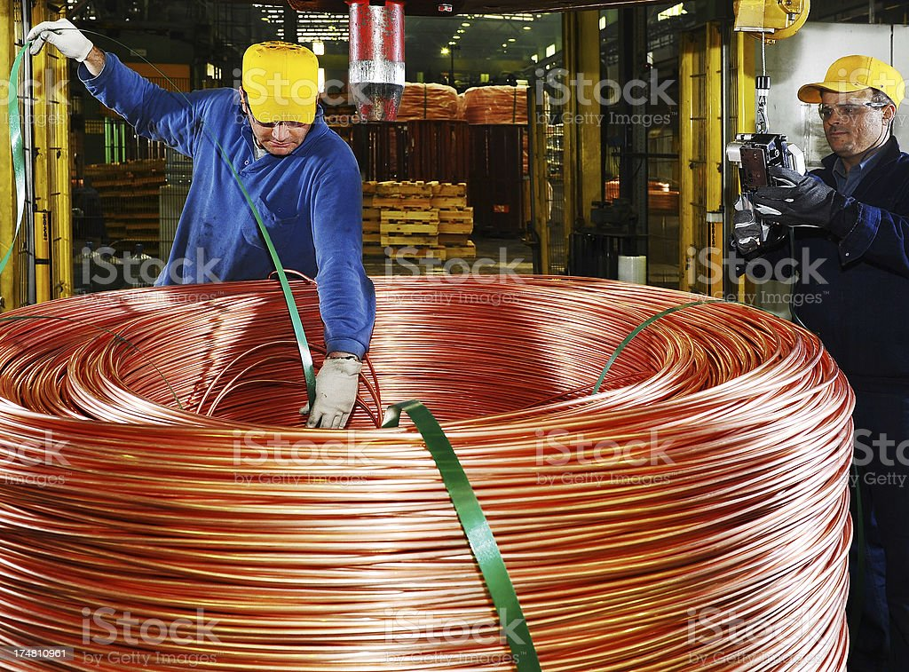 Workers use a hoist to stack huge copper coil royalty-free stock photo