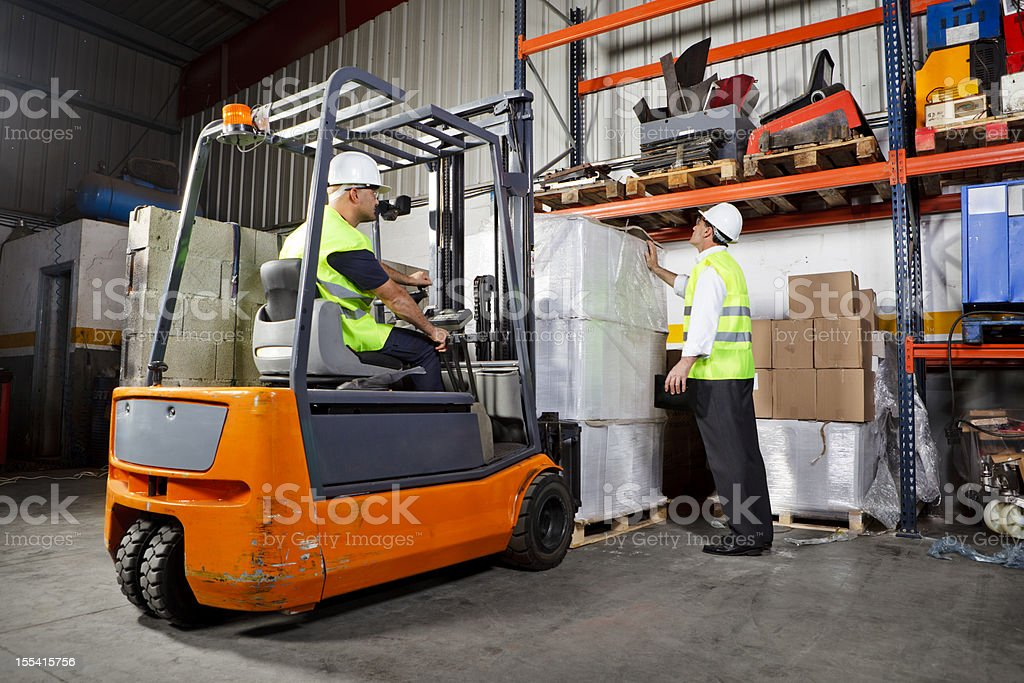 Workers Using Forklift in Warehouse stock photo