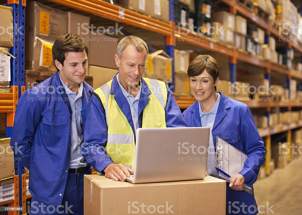 Workers using laptop in warehouse stock photo