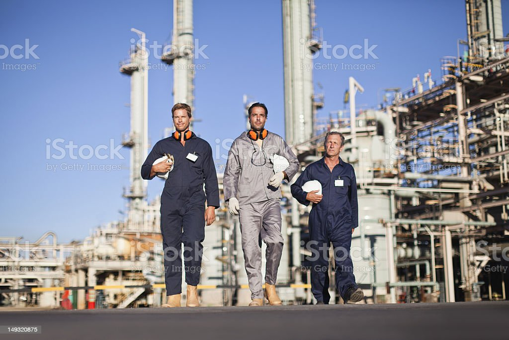 Workers walking at oil refinery stock photo