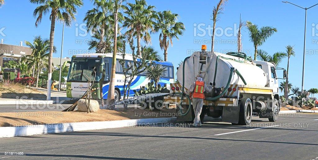 Workers watering roadside plants in San Jose Del Cabo stock photo