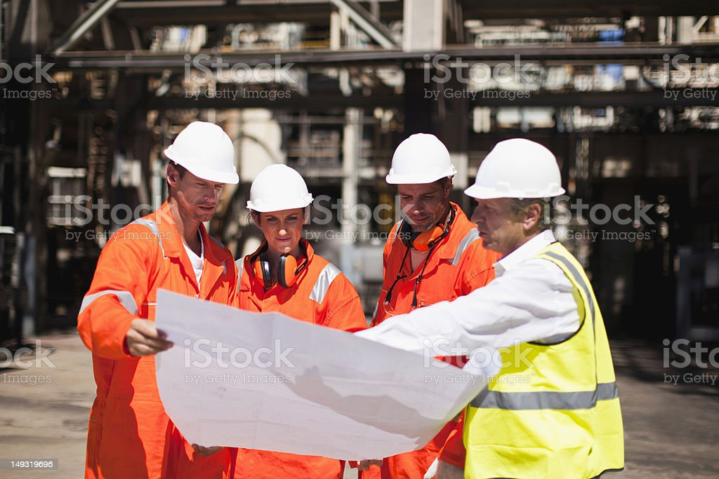 Workers with blueprints at oil refinery stock photo