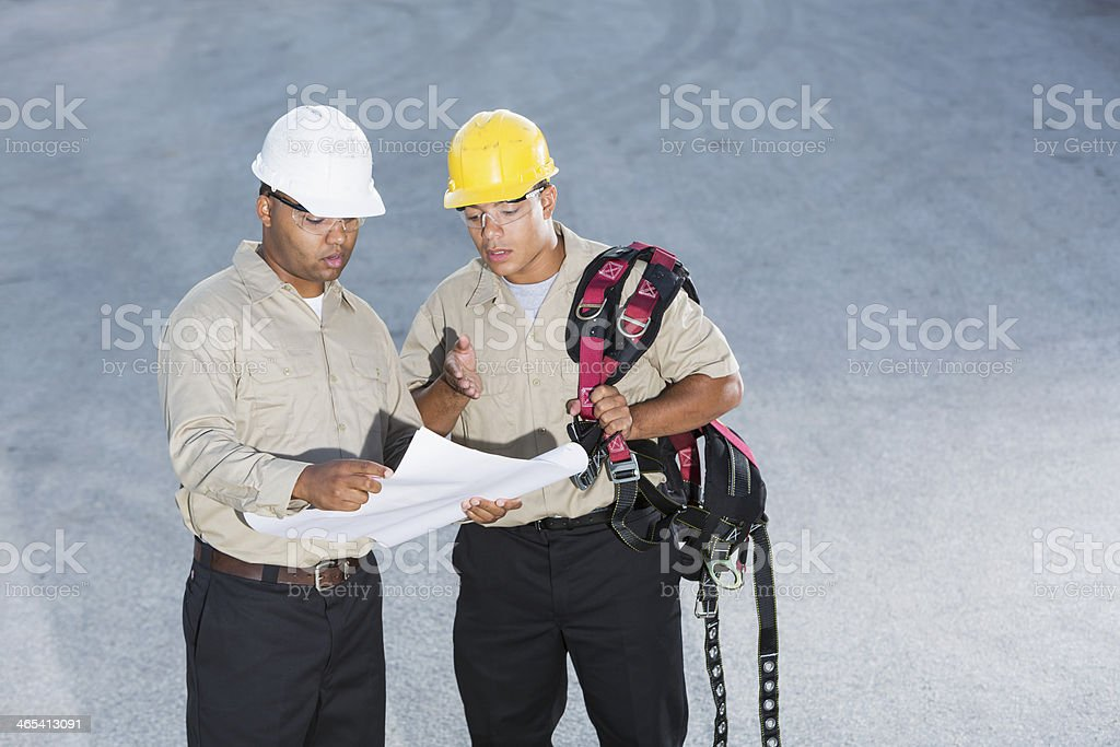 Workers with hardhats and harness, reading plans stock photo