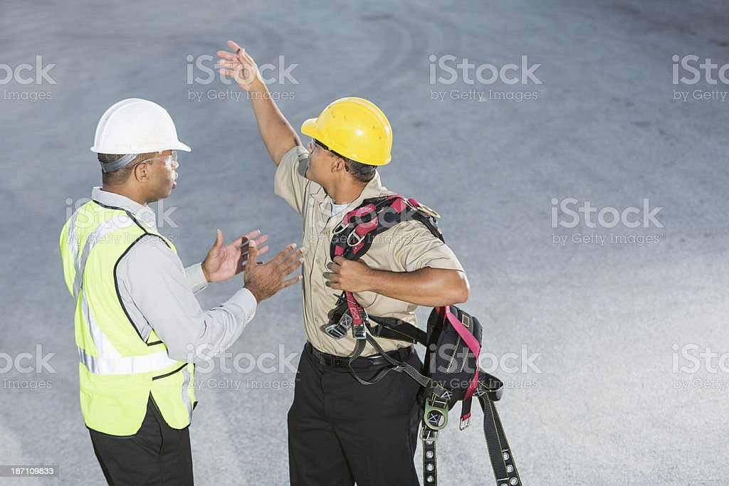 Workers with hardhats, safety vest and harness stock photo