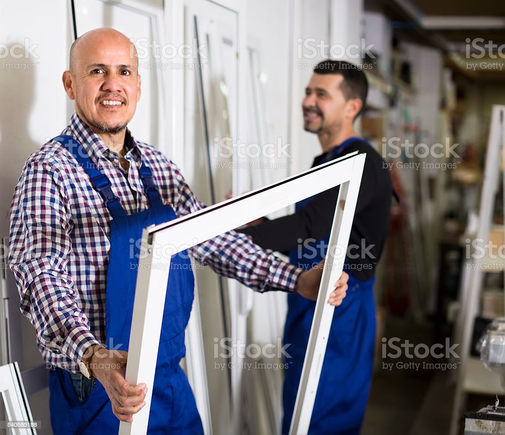 Workers with PVC windows and doors stock photo