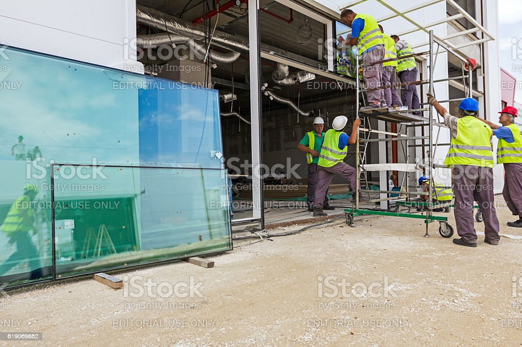 Workers with suction cup are holding glass to complete window. stock photo