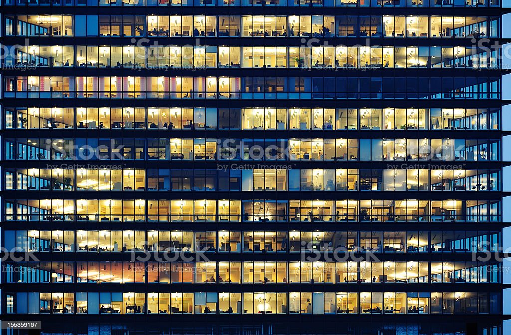 Workers working late. Office windows by night. stock photo