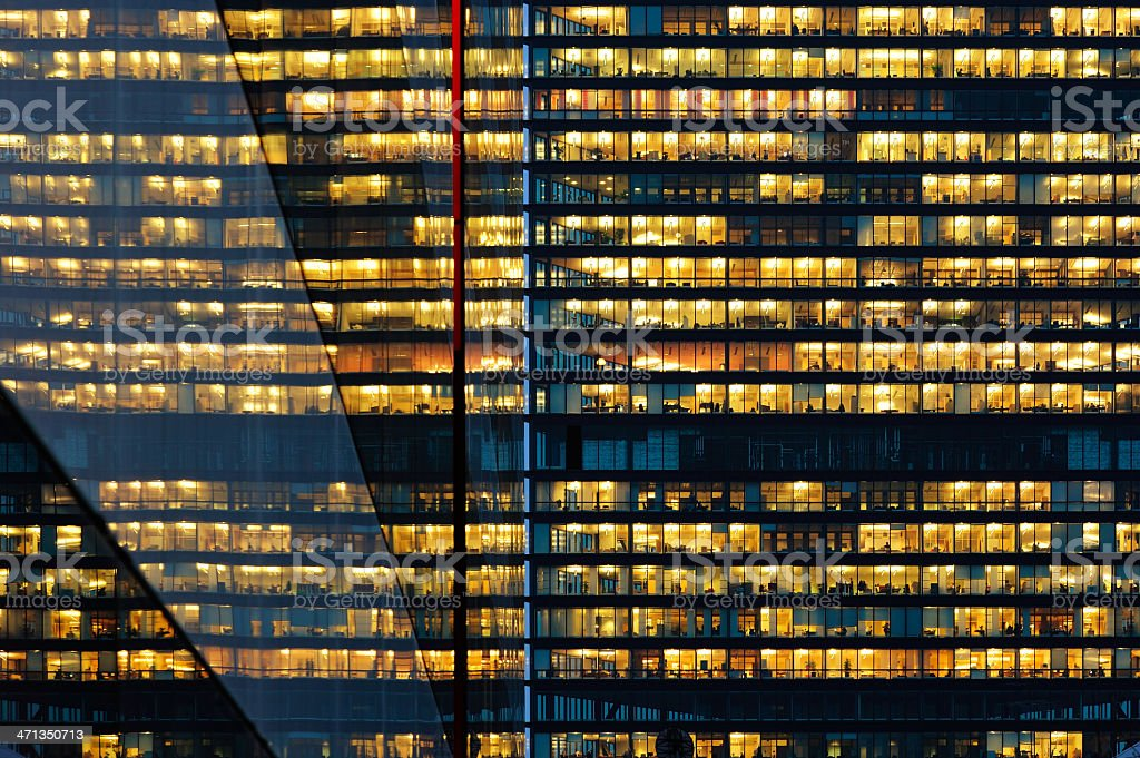 Workers working late. Reflection in neighbour building royalty-free stock photo