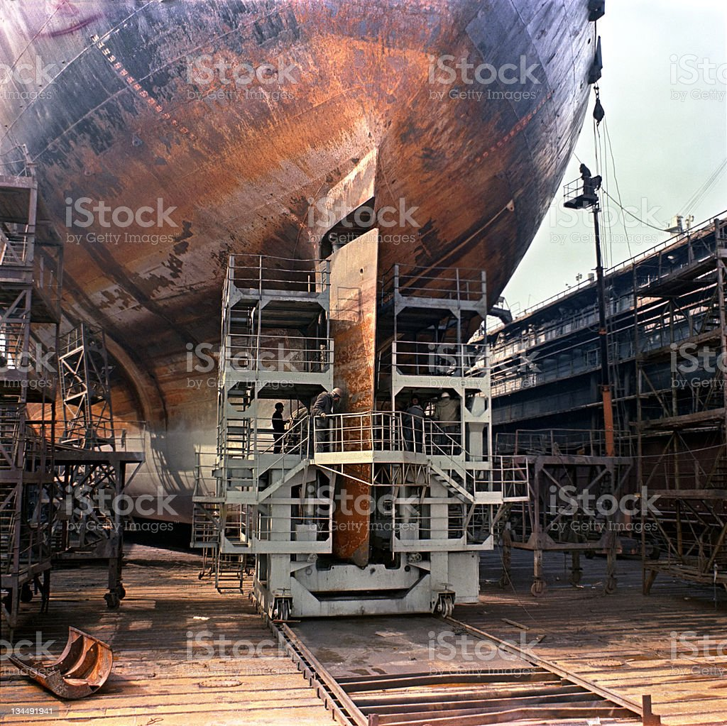 Workers working on a big ship while docked royalty-free stock photo