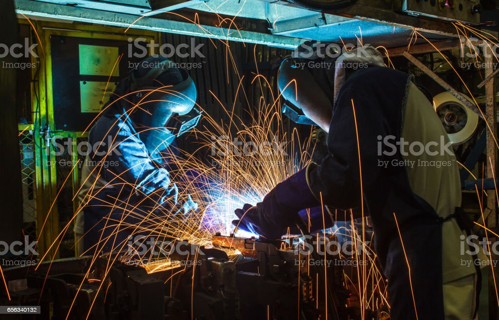 Worker,welding in a car factory with sparks stock photo