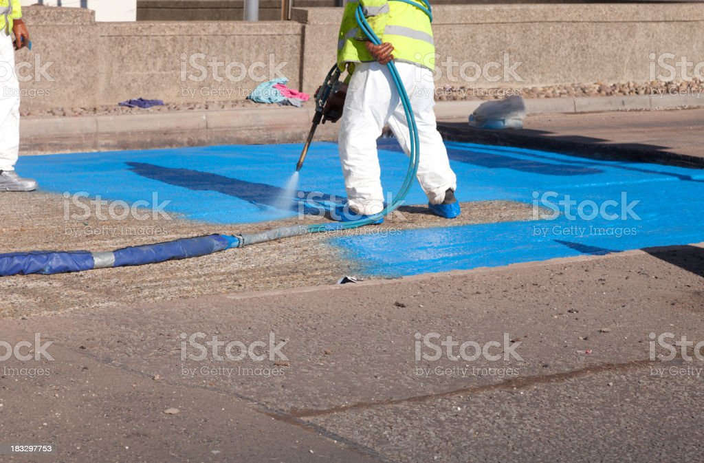 Workforce spraying a waterproof layer membrane to new road construction stock photo
