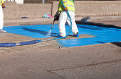 Workforce spraying a waterproof layer membrane to new road construction