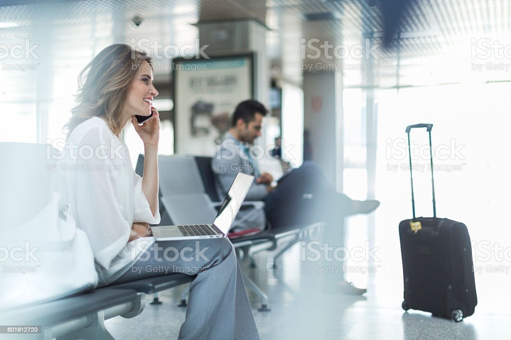 Working and using phone while waiting on departure gate. stock photo
