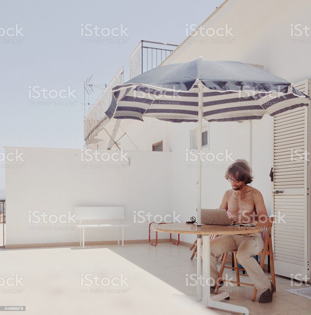 Working at home in the sun of a balcony stock photo