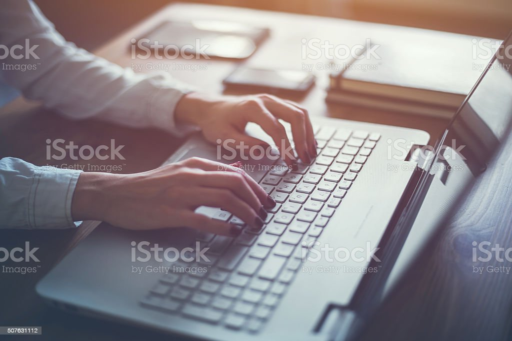 Working at home with laptop woman writing a blog. Female stock photo