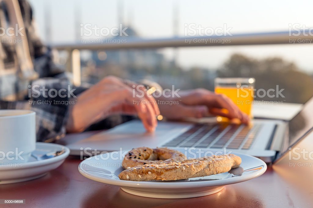 Working Breakfast Person Working on Laptop at Cafe Terrace stock photo