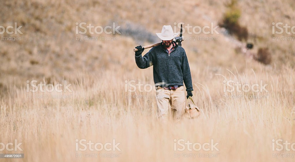 Working cowboy walks through hay field carrying pickaxe and toolbag stock photo