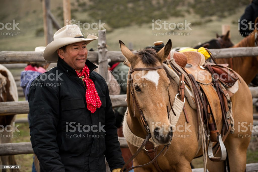 Working cowboy with his saddled buckskin horse at the corral stock photo