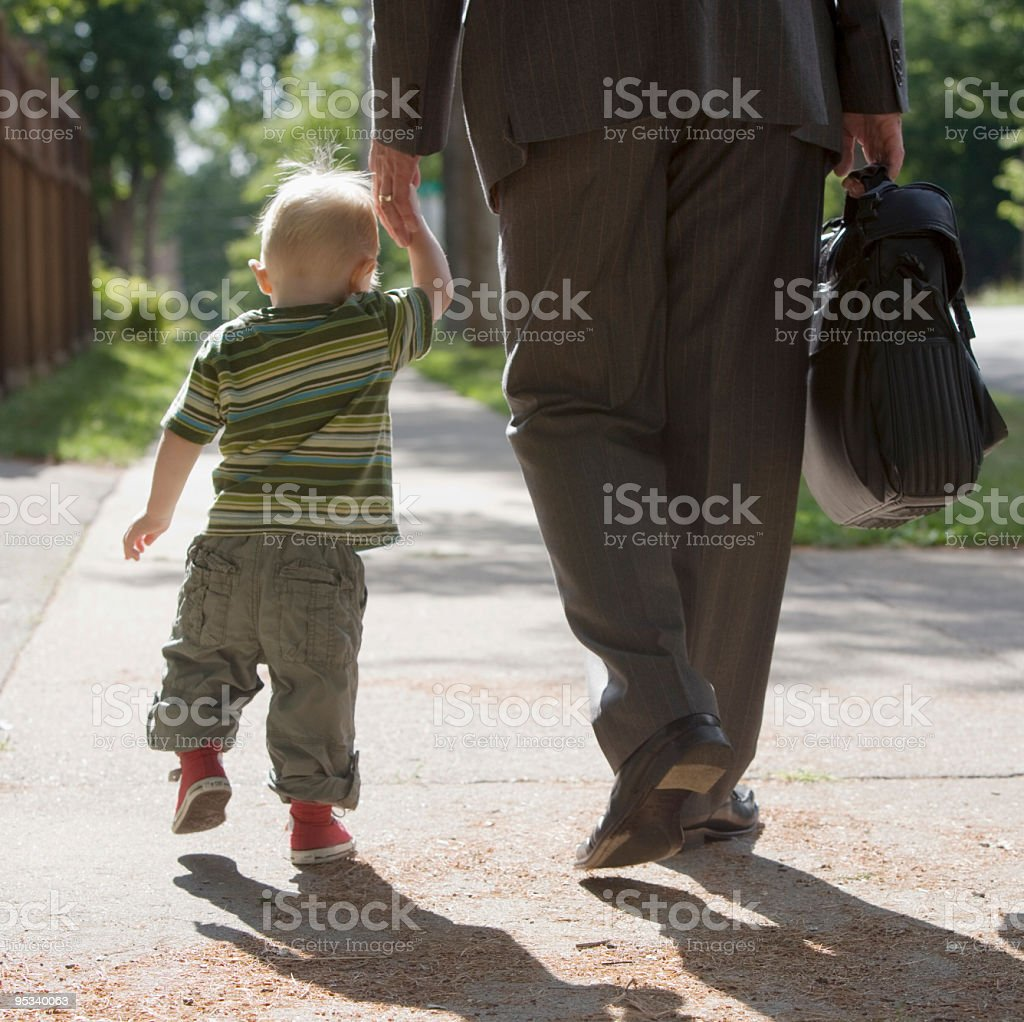 Working Dad walking with son stock photo