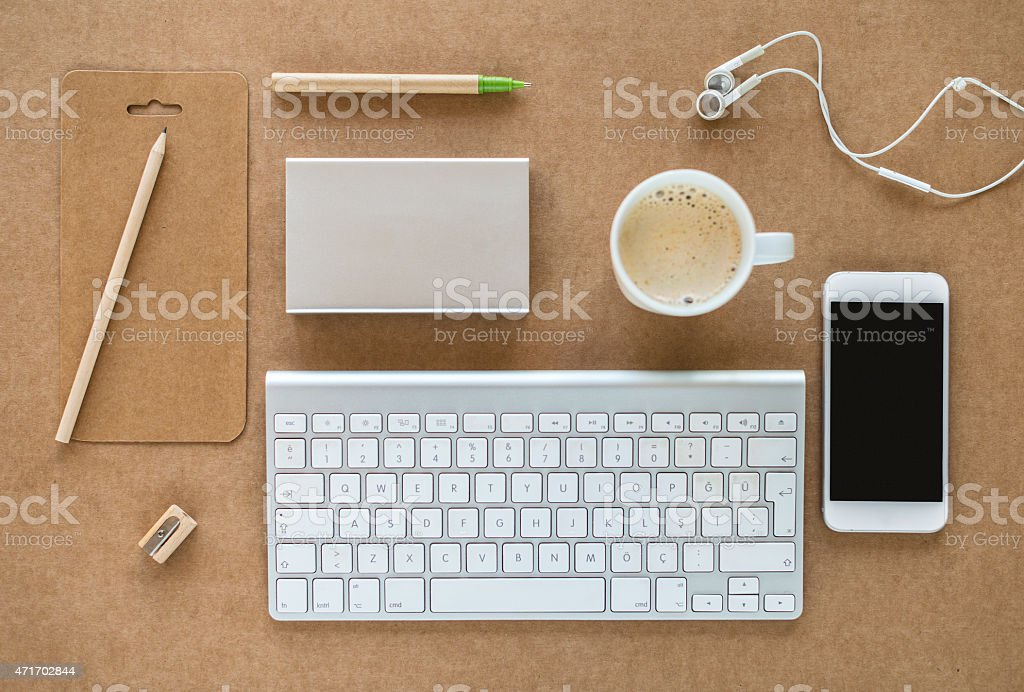Working desk with keyboard, coffee, cell phone and headphones stock photo