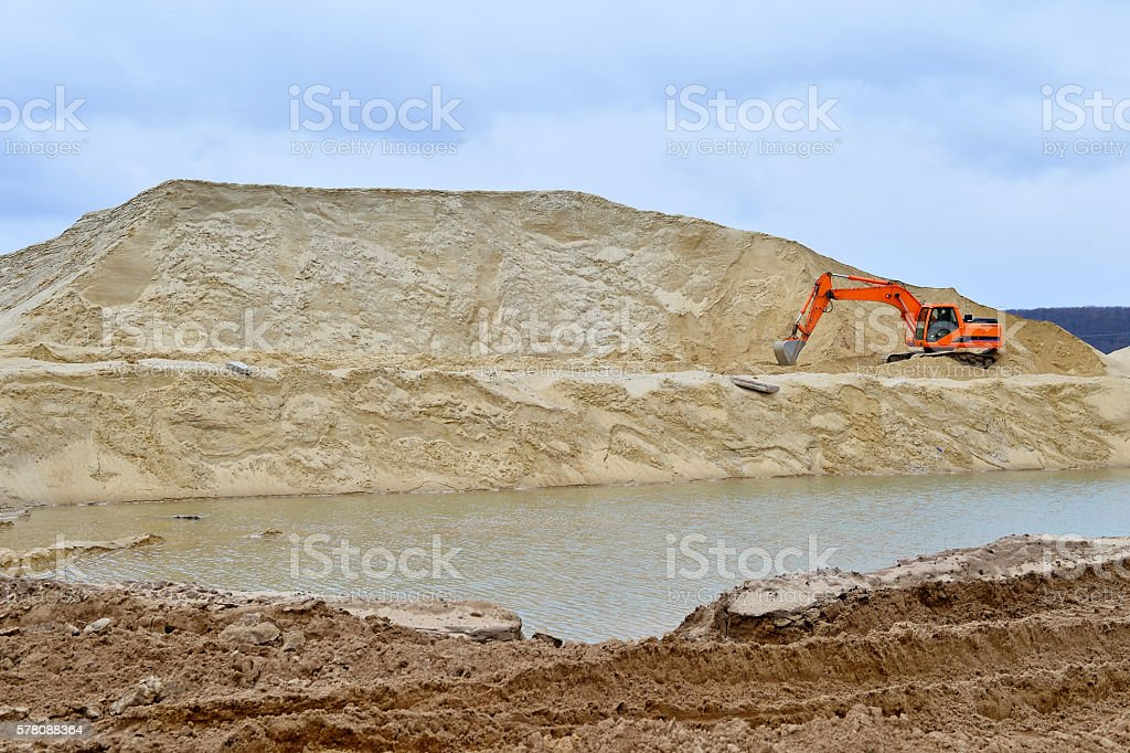 Working digger in a quarry produces sand stock photo