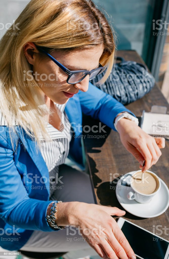 Working girl stiring coffee and looking phone stock photo