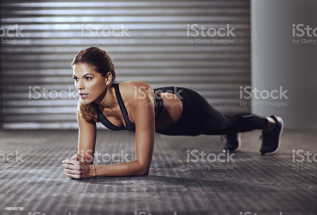 Working her core muscles to the max with some planks stock photo