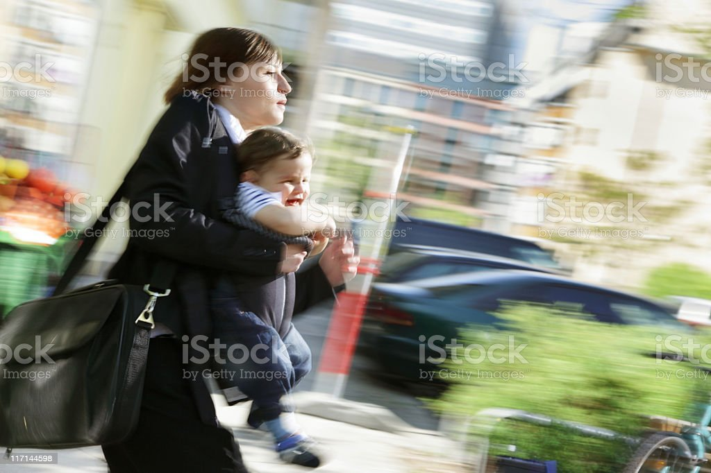 Working in a rush, mom carrying infant son outdoors stock photo