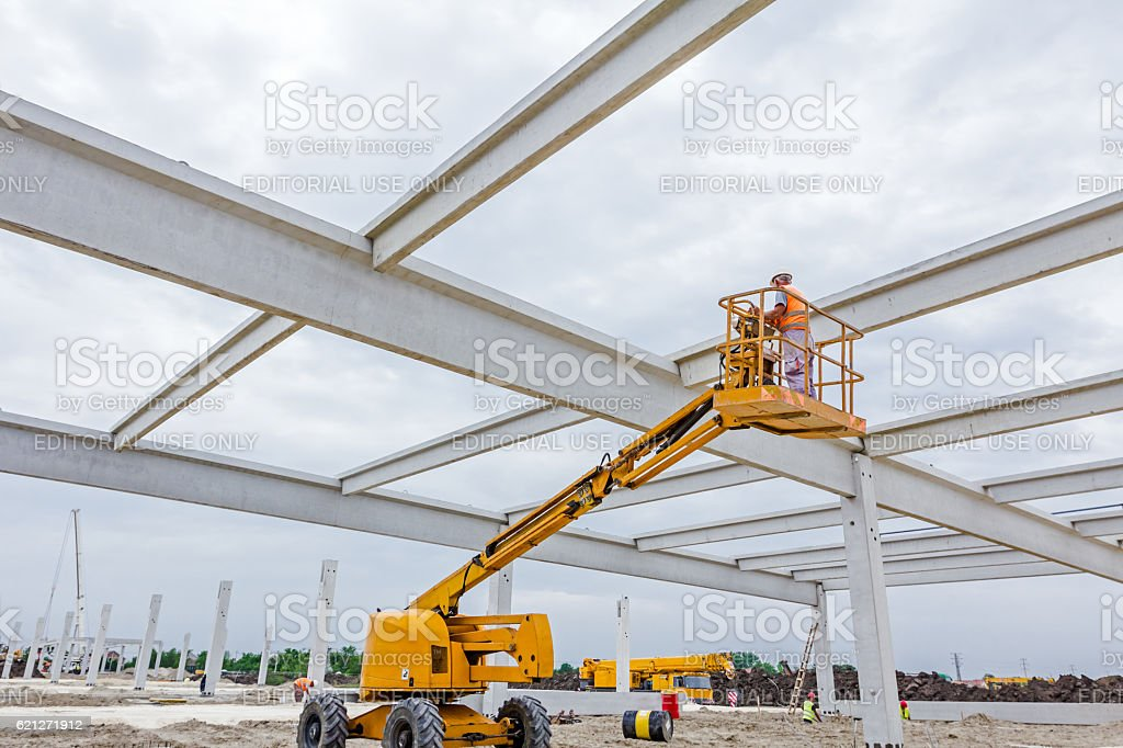 Working in elevated cherry picker on building site stock photo