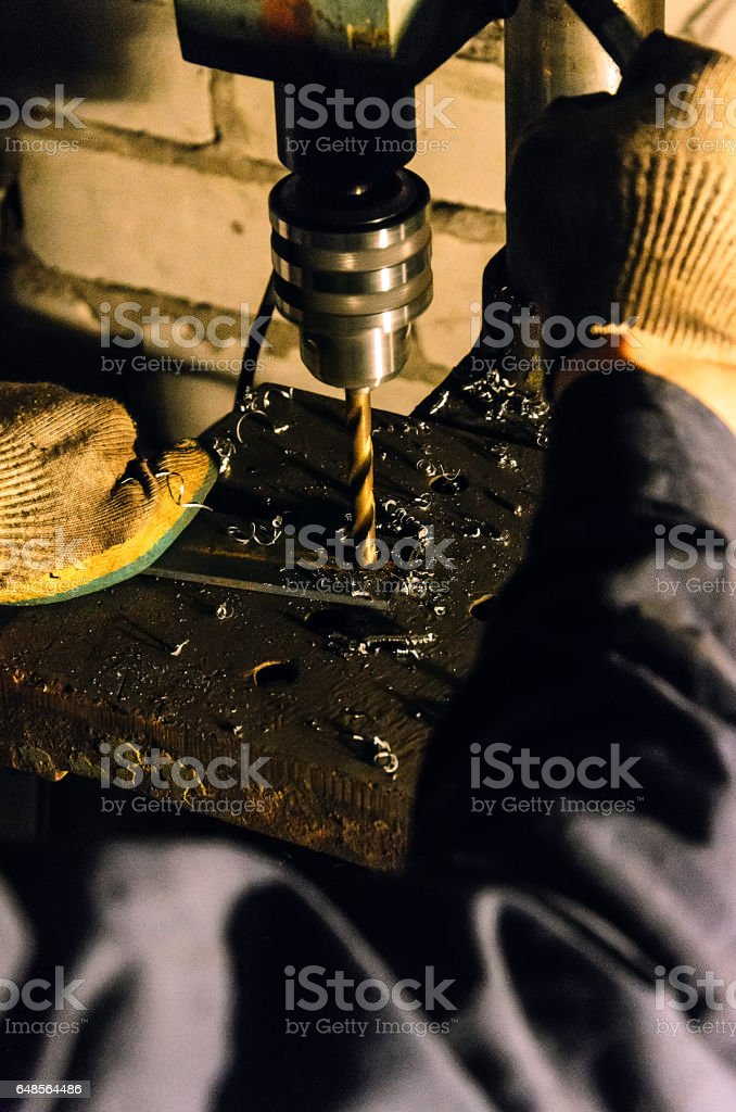 working in the workshop, which is on the drill press drill metal parts. He wore overalls and dirty gloves stock photo