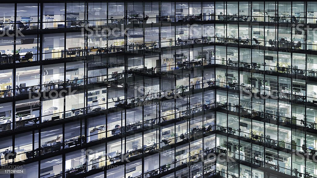 Working late, office windows by night stock photo