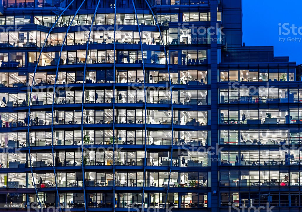 Working late. Office windows by night. stock photo