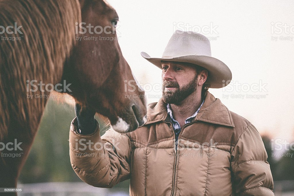 Working man with cowboy hat stands petting horse royalty-free stock photo
