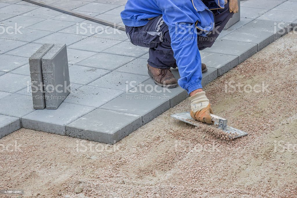 working on gravel flattening before lay patio pavers stock photo