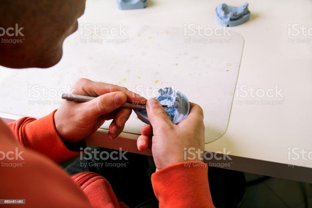 Working on he plaster model of the jaw. Dentures. Dental prosthesis, dentures, prosthetics work. Dental technician in process of making dentures. Technician is working on he plaster model of the jaw. stock photo