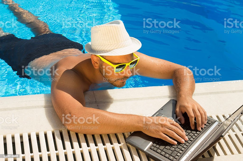 Working on laptop from the swimming pool stock photo
