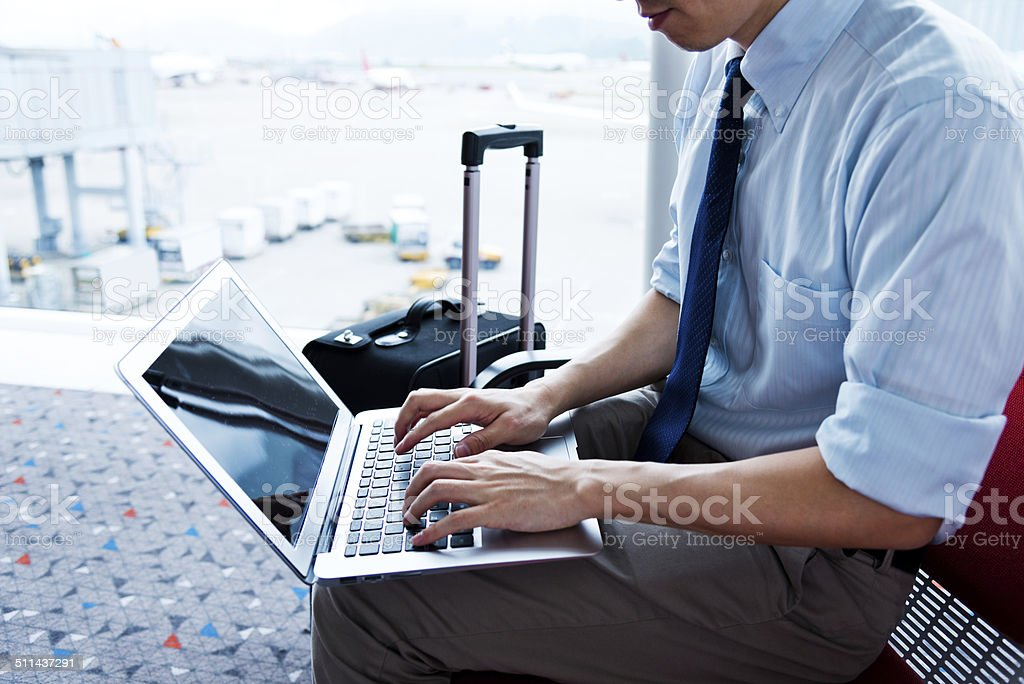 working on laptop in the airport stock photo