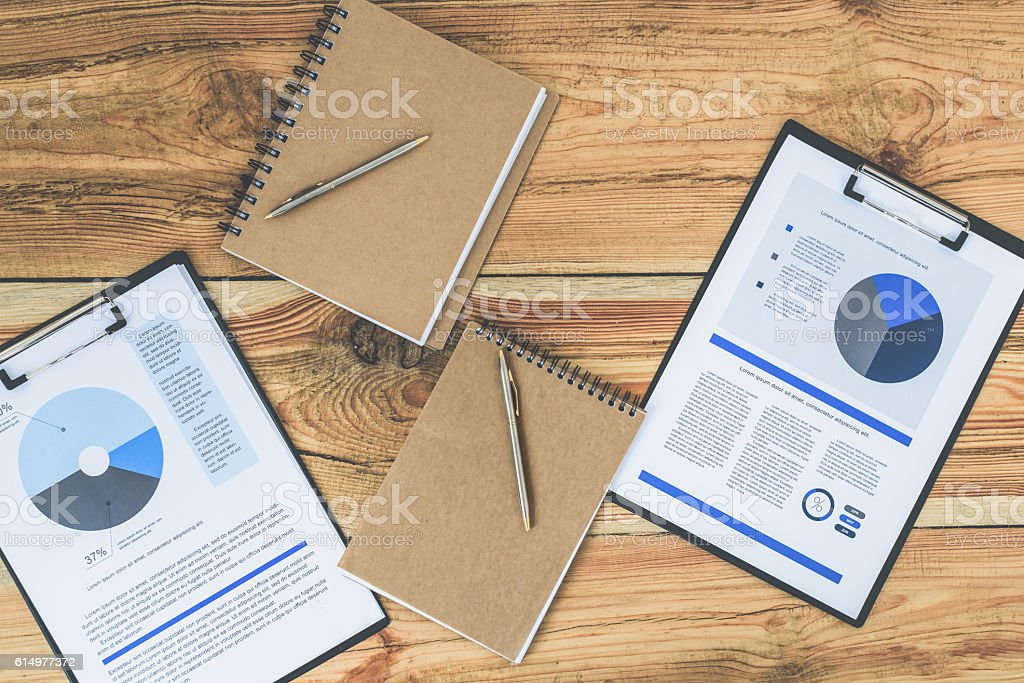 Working papers and writing-pads on desk stock photo