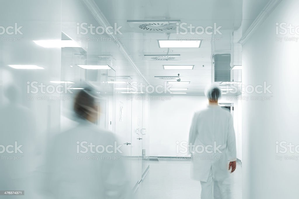 Working people with white uniforms walking in modern  factory environment stock photo