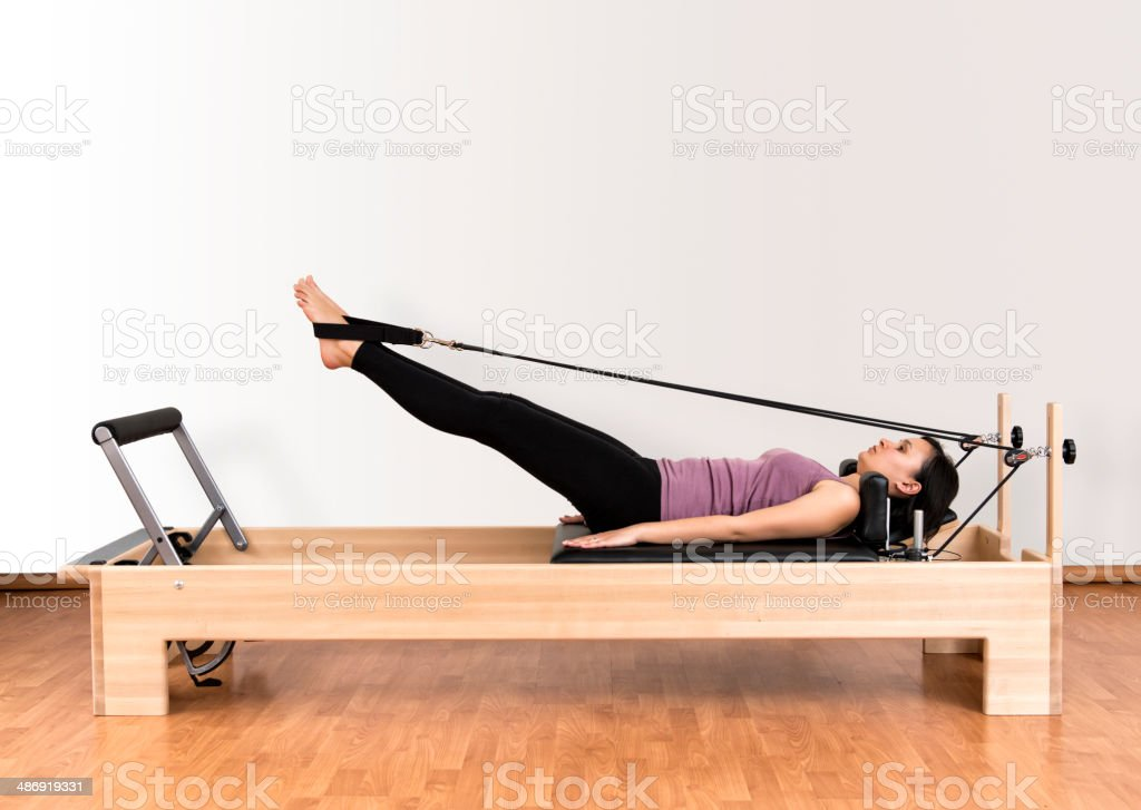 Working Pilates on Reformer Bed stock photo