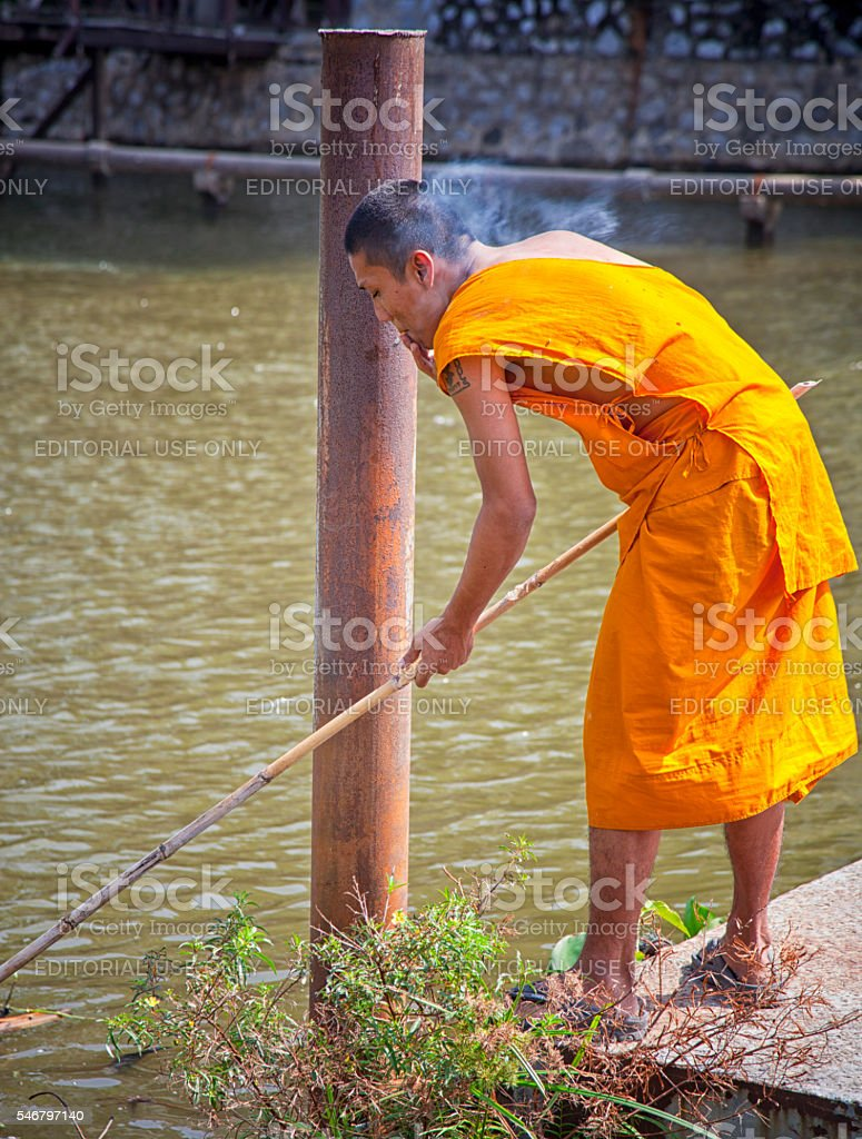 Working, smoking thai monk. stock photo