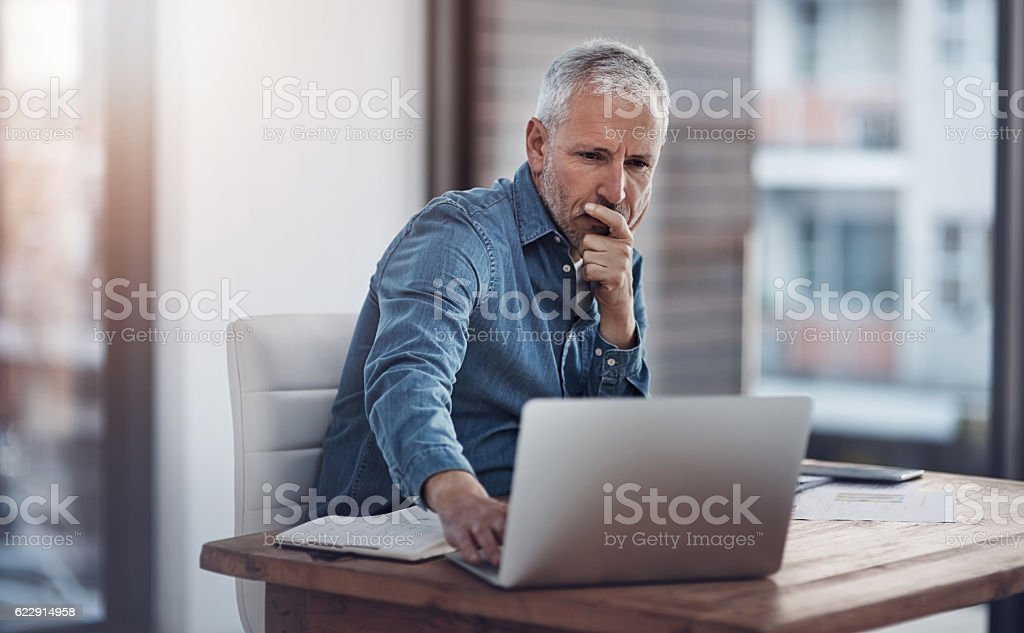 Working through ways to better manage his business stock photo