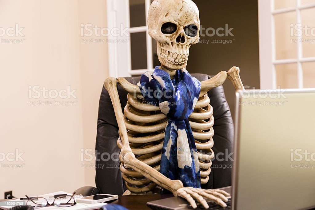 Working to death.  Business woman's skeleton using laptop in office. stock photo