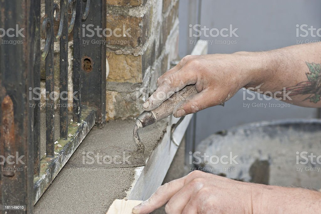 Working to polish a staircase with mortar and trowel royalty-free stock photo