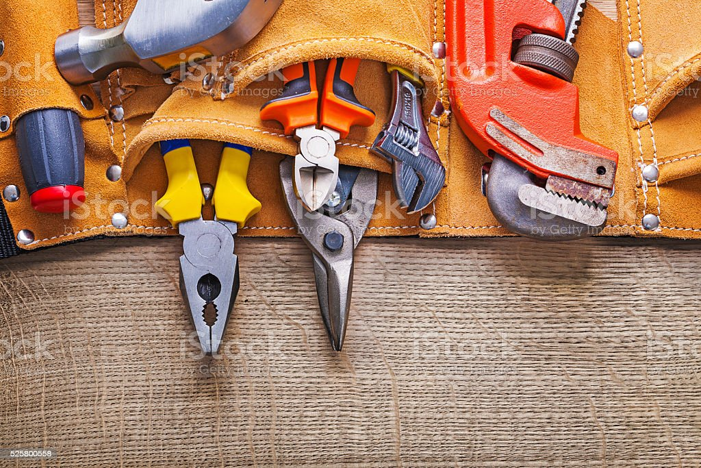 working tools in toolbelt on wooden board stock photo