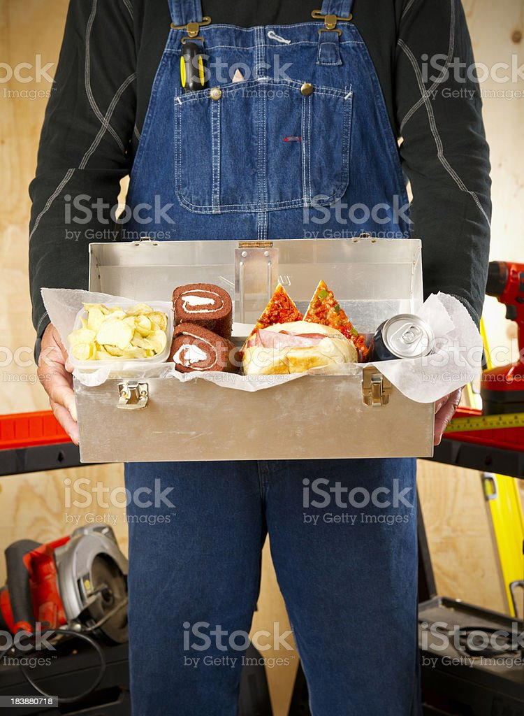 Working tradesman with an unhealthy box lunch stock photo