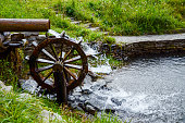 Working watermill wheel with falling waterin the village.