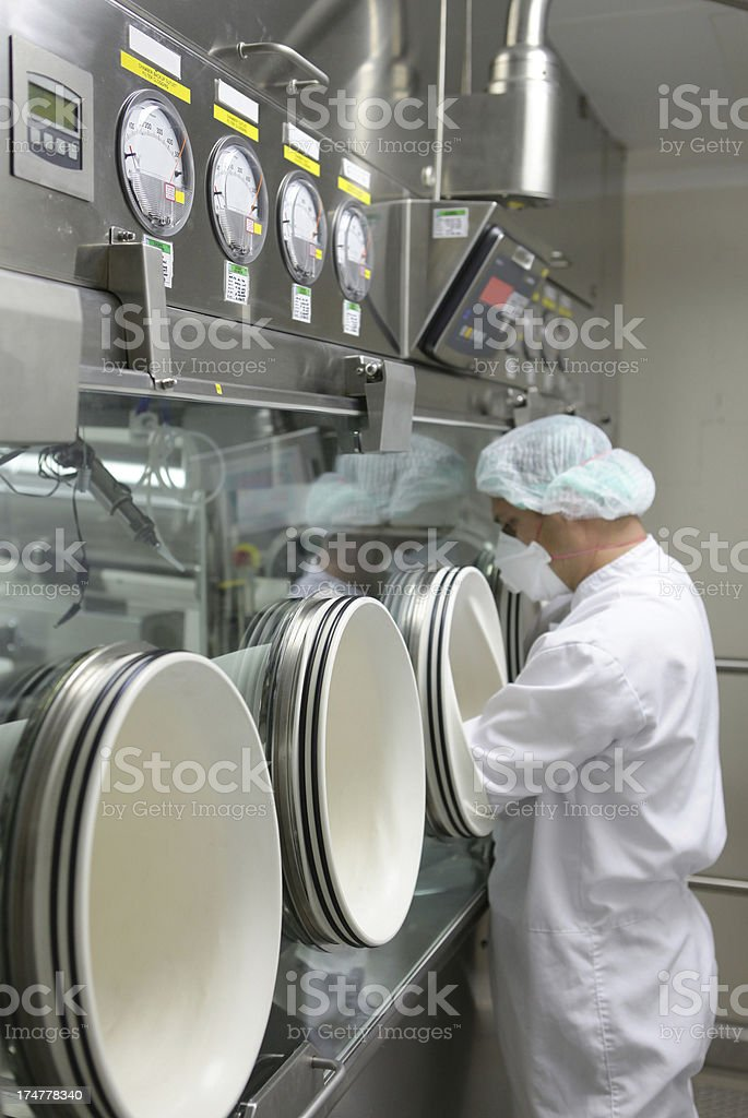 Working with glove box  machine in pharmaceutical factory stock photo